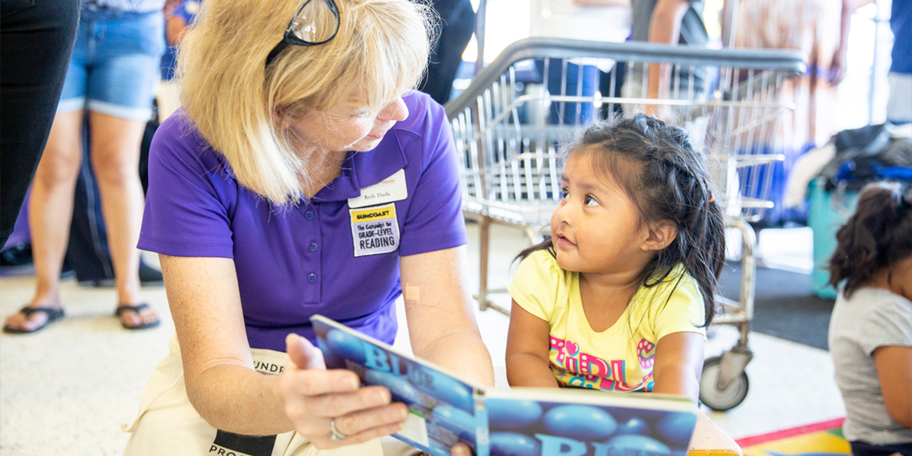 Beth Duda reads to an adorable toddler in a laundromat