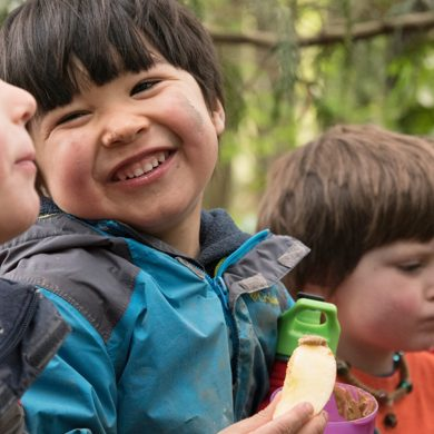 Kids with dirt smudges on their faces, laughing and eating outdoors
