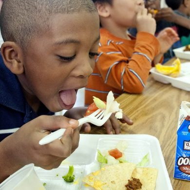 A young boy takes a bite of a school meal