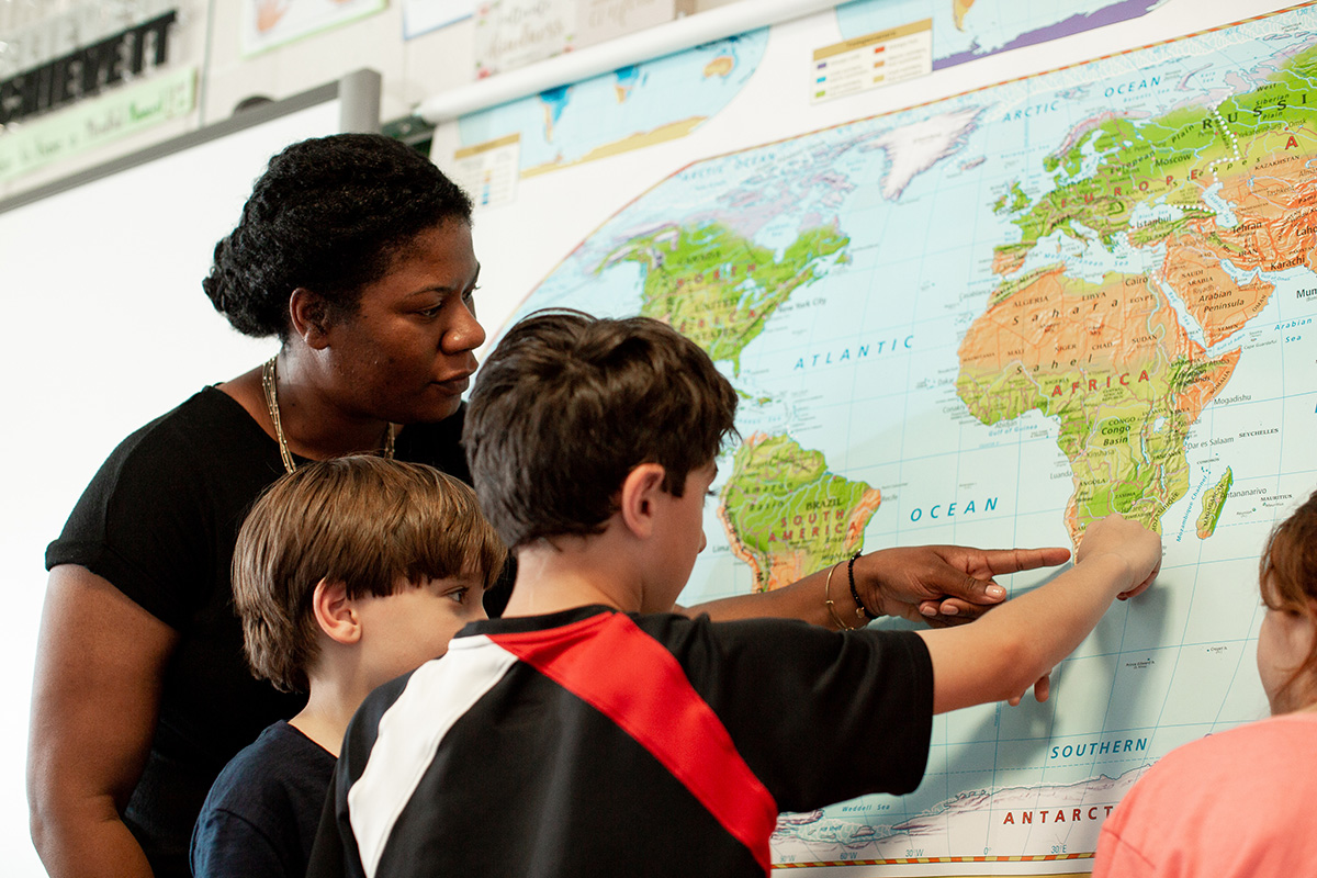 A group of children and their teacher/leader point to a global map together