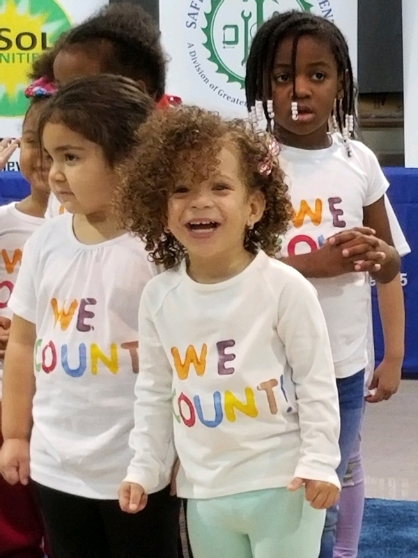 "Smiling and laughing children wearing ""We Count"" t-shirts"