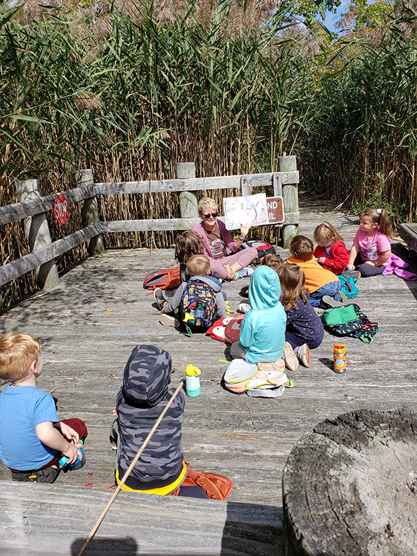 A woman reads outside in the sunshine to a group of children on a deck