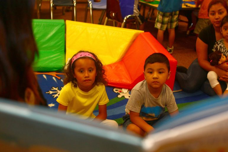 Children facing a story book that's being read to them