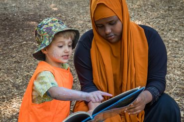 A woman reads a book outdoors with a small boy who has paint and dirt on his face.