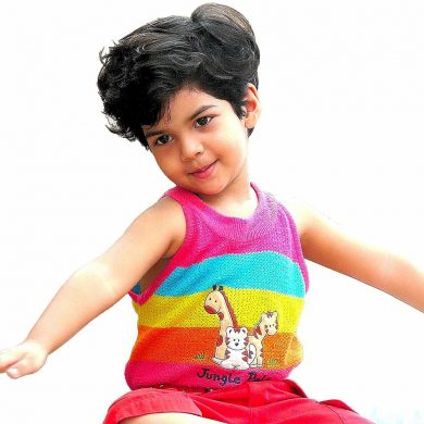 A young child wearing a rainbow tank top stretches